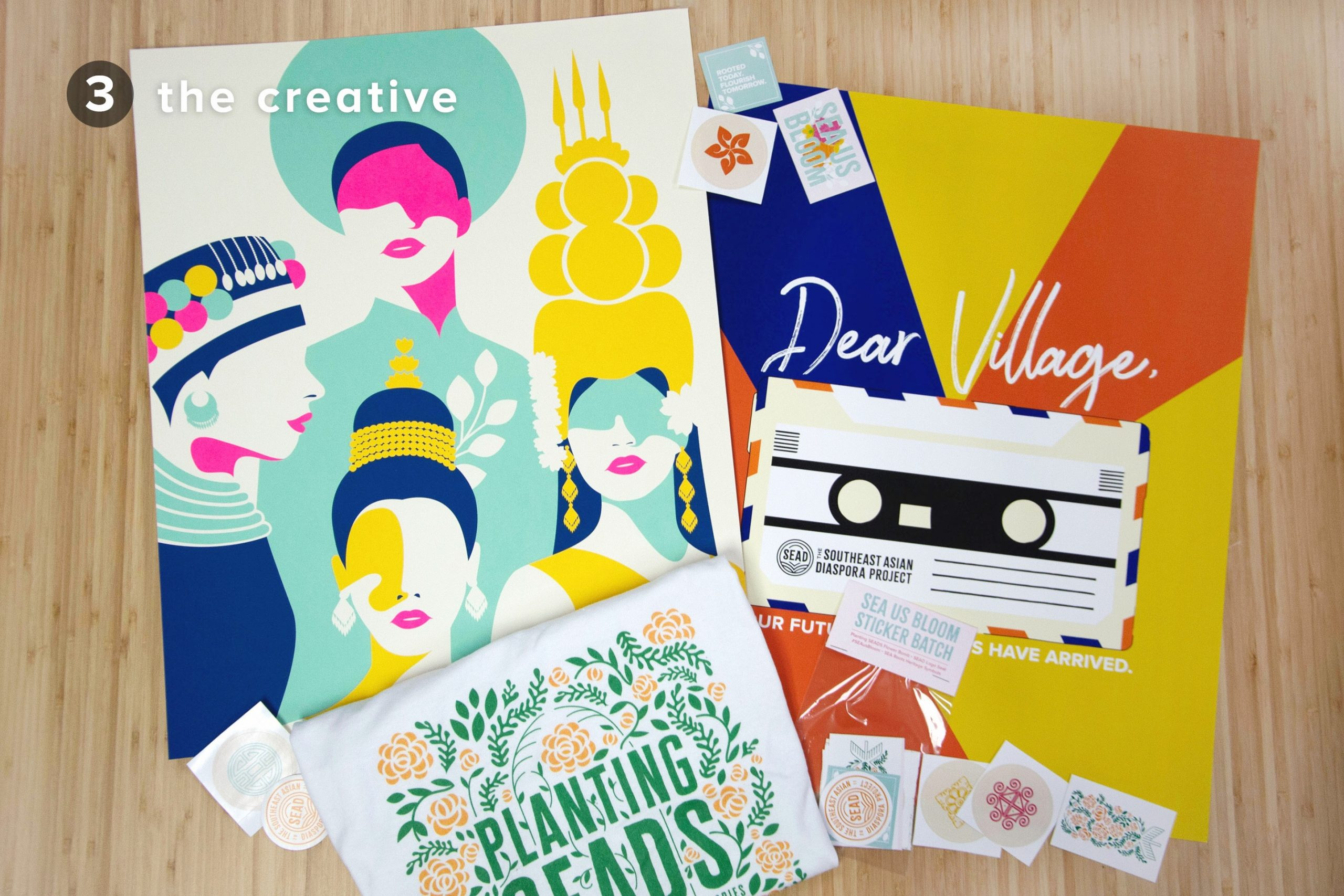 The Creative: SEA Queens poster, Dear Village poster, Planting SEADS t-shirt, SEA Us Bloom sticker batch